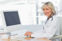 Female doctor using computer at desk in medical office Stock Photo