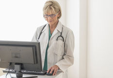 Female Doctor Using Desktop PC At Desk Stock Photo