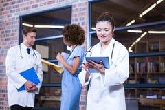 Female doctor using digital tablet near library Stock Photos