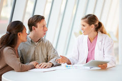 Female Doctor Using Digital Tablet Talking With Patients Royalty Free Stock Image