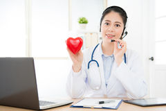 Female doctor using headphone to conversation. Smiling female doctor using headphone to conversation at clinic office with cardiology patient using online royalty free stock photography