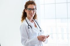 Female doctor using her digital tablet in the office. Royalty Free Stock Images