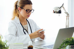 Female doctor using his mobile phone in the office. Stock Images