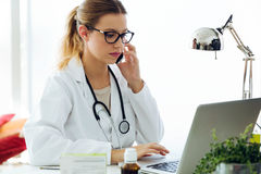 Female doctor using his mobile phone in the office. Stock Photos