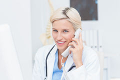 Female doctor using land line phone in clinic. Portrait of confident female doctor using land line phone in clinic Stock Images