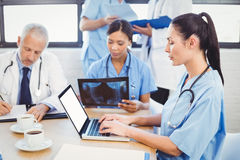 Female doctor using laptop in conference room Stock Photo