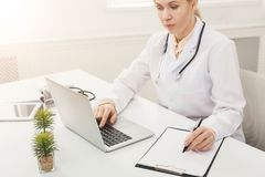 Female doctor using laptop and writing notes. While working at her office. Always ready to help, medicine concept, copy space Royalty Free Stock Photography
