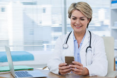 Female doctor using mobile phone with laptop on table Royalty Free Stock Photos