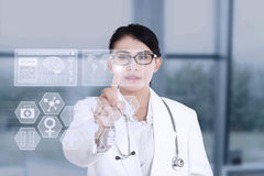 Female doctor using modern technology. Female doctor touching medical interface on modern technology stock photography