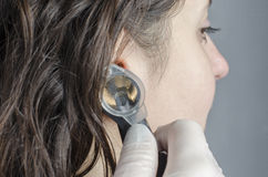 Female doctor using otoscope with a girl patient. Royalty Free Stock Image