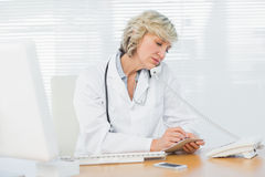 Female doctor using phone by computer at medical office Stock Photography