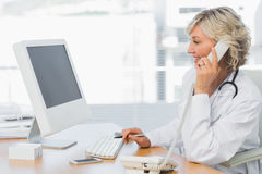 Female doctor using phone at desk in medical office Stock Photography