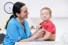 Doctor using stethoscope to examining little sweet boy stock photo