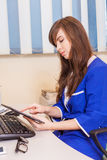 Female doctor using a tablet computer in a hospital. She is wear Royalty Free Stock Photos