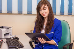 Female doctor using a tablet computer in a hospital. She is wear Stock Photo