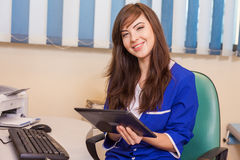 Female doctor using a tablet computer in a hospital. She is wear Stock Photography