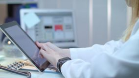 Female doctor using tablet at medical workplace. Nurse using tablet pc. Close up of medical specialist touch tablet screen. Woman doctor working with ipad stock video footage