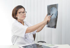 Female doctor watching on head skull x-ray film Stock Photos