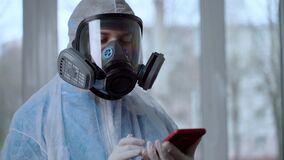 Female Doctor Wearing a Facemask and Suit sand informatiom by mobile phone. Medic wears a protective suit and mask