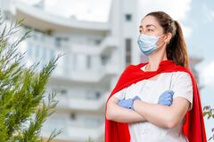 A female doctor wearing a surgical mask and rubber gloves poses with her arms crossed and a super hero's cape on her back