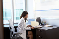 Female Doctor Wearing White Coat Reading Notes In Office Royalty Free Stock Photo