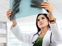 Female doctor wearing a white coat and stethoscope looking at an Stock Photo