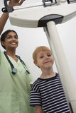 Female Doctor Weighting Young Patient. Portrait of a happy boy standing on weighing machine while female doctor checking weight stock photo