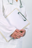Female doctor in white uniform posing with blank clipboard pad Royalty Free Stock Image