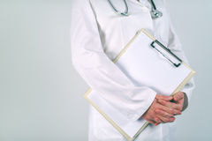 Female doctor in white uniform posing with blank clipboard pad Royalty Free Stock Photography