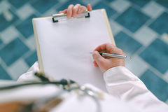 Female doctor in white uniform writing on clipboard paper Stock Photo
