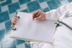 Female doctor in white uniform writing on clipboard paper Royalty Free Stock Photos