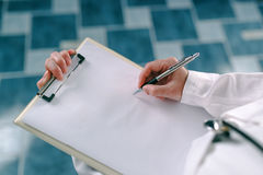 Female doctor in white uniform writing on clipboard paper Royalty Free Stock Image
