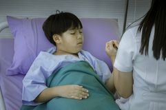 Female doctor who sits on sick child`s bed. Use hand to hold hands. Encourage patient influenz to sleep in hospital stock photo