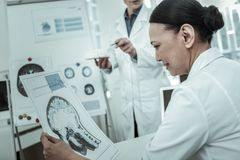 Female doctor during workday attentively looking on the photo. Discussing brain disease. Female doctor during workday attentively looking on the photo of brain stock images