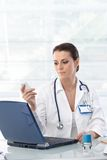 Female doctor working at desk Royalty Free Stock Images