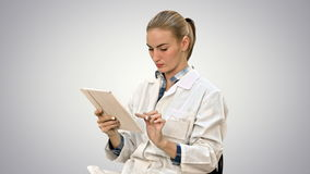 Female doctor working on digital tablet on white background. stock footage