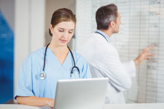 Female doctor working on laptop with colleague pointing at chart Royalty Free Stock Photo