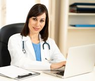 Female doctor working on medical expertise and searching information on laptop at hospital office. Portrait of happy attractive woman doctor in white coat stock photo