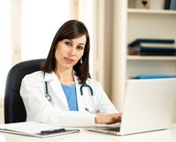 Female doctor working on medical expertise and searching information on laptop at hospital office. Portrait of happy attractive woman doctor in white coat royalty free stock photo