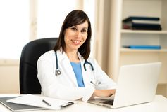 Female doctor working on medical expertise and searching information on laptop at hospital office. Portrait of happy attractive woman doctor in white coat stock photos