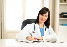 Female doctor working on medical expertise and searching information on laptop at hospital office. Portrait of happy attractive woman doctor in white coat royalty free stock images