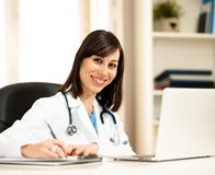 Female doctor working on medical expertise and searching information on laptop at hospital office. Portrait of happy attractive woman doctor in white coat stock images