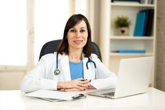 Female doctor working on medical expertise and searching information on laptop at hospital office. Portrait of happy attractive woman doctor in white coat stock image