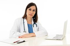 Female doctor working on medical expertise and searching information on laptop at hospital office. Portrait of natural looking woman doctor working with laptop royalty free stock image