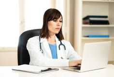 Female doctor working on medical expertise and searching information on laptop at hospital office. Portrait of successful attractive woman doctor in white coat royalty free stock images