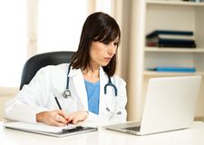 Female doctor working on medical expertise and searching information on laptop at hospital office. Portrait of successful attractive woman doctor in white coat stock image