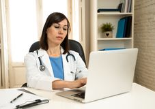 Female doctor working on medical expertise and searching information on laptop at hospital office. Portrait of successful attractive woman doctor in white coat royalty free stock photography
