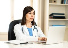 Female doctor working on medical expertise and searching information on laptop at hospital office. Portrait of successful attractive woman doctor in white coat stock photo