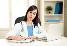 Female doctor working on medical expertise and searching information on laptop at hospital office. Portrait of successful attractive woman doctor in white coat royalty free stock photos