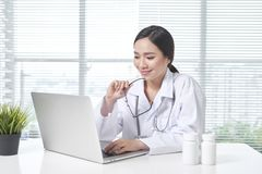 Female doctor working at office desk and smiling at camera stock photos